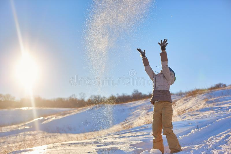 Beauty Winter Girl Blowing Snow in frosty winter Park. Outdoors. Flying Snowflakes. Sunny day. Backlit. Beauty young woman Having stock images