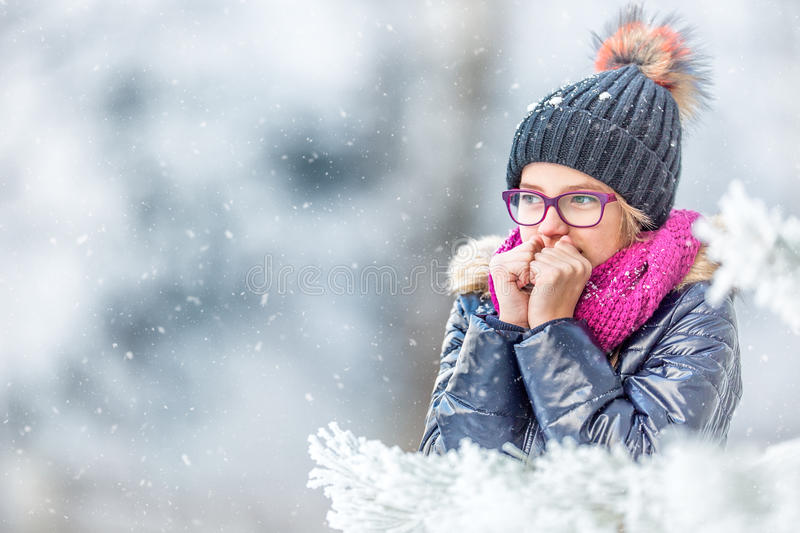 Beauty Winter Girl Blowing Snow in frosty winter park or outdoors. Girl and winter cold weather stock photos