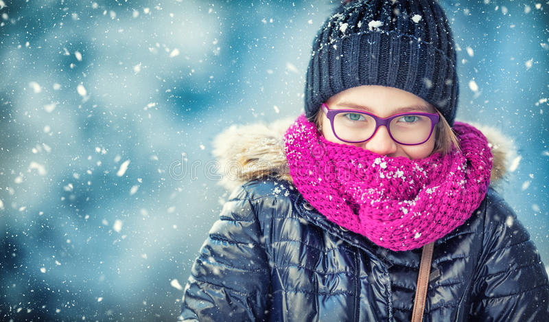 Beauty Winter Girl Blowing Snow in frosty winter park or outdoors. Girl and winter cold weather.  stock photo