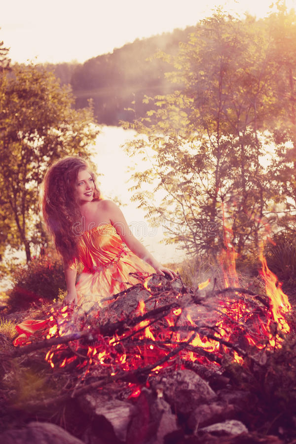 Beauty witch in the woods near the fire. Magic woman celebrating stock photography