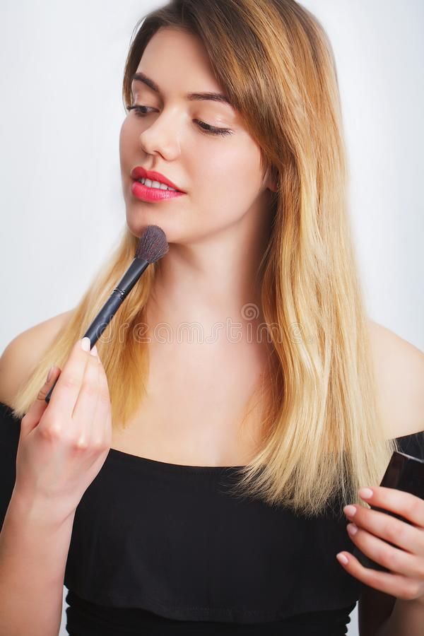 Beauty woman applying makeup. Beautiful girl looking in the mirror and applying cosmetic with a big brush royalty free stock images