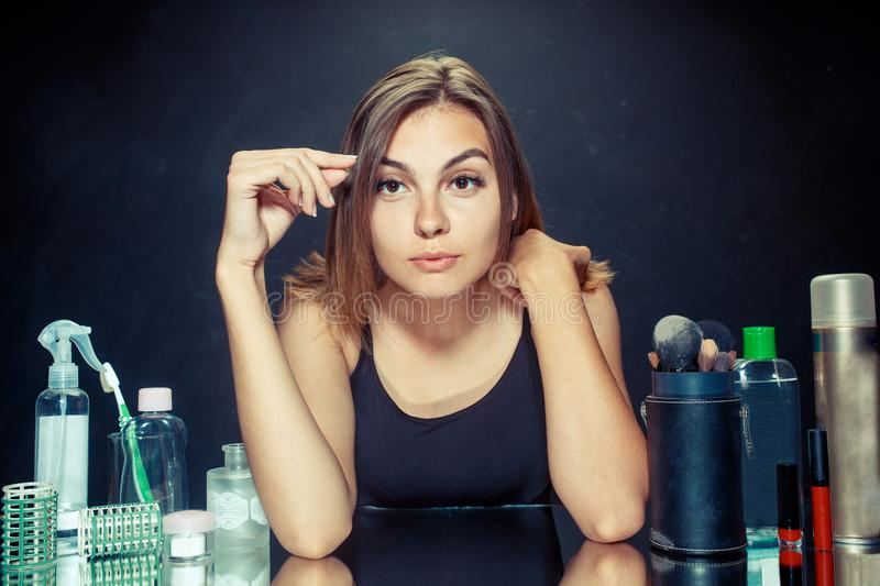 Beauty woman applying makeup. Beautiful girl looking in the mirror and applying cosmetic with a big brush. stock photography