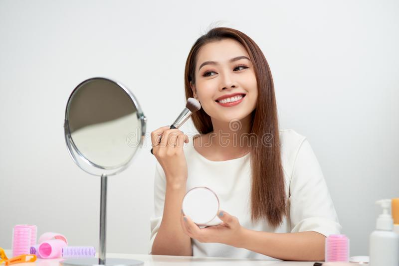 Beauty woman applying makeup. Beautiful girl looking in the mirror and applying cosmetic with a big brush. Girl gets blush on the royalty free stock photography