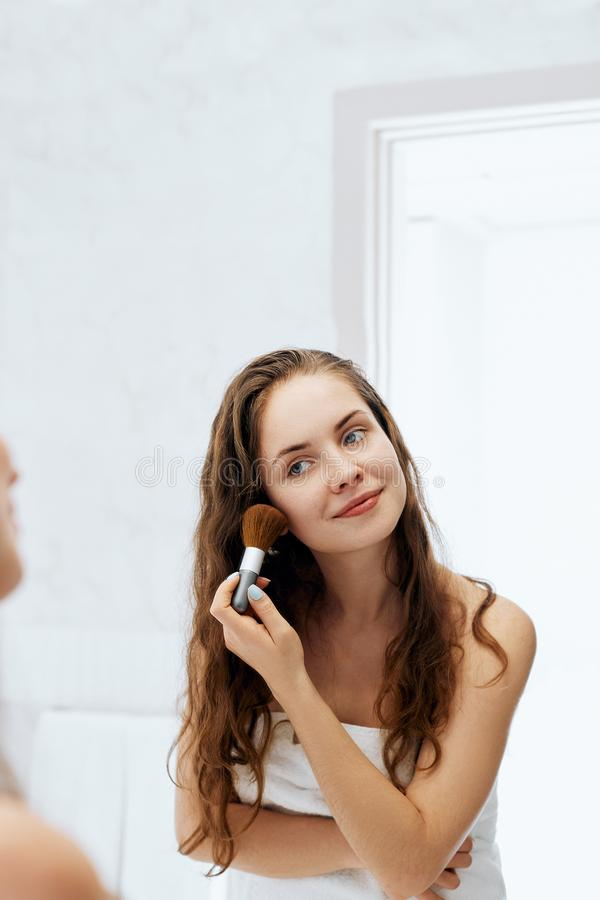 Beauty woman applying makeup. Beautiful girl looking in the mirror and applying cosmetic with a big brush royalty free stock photos