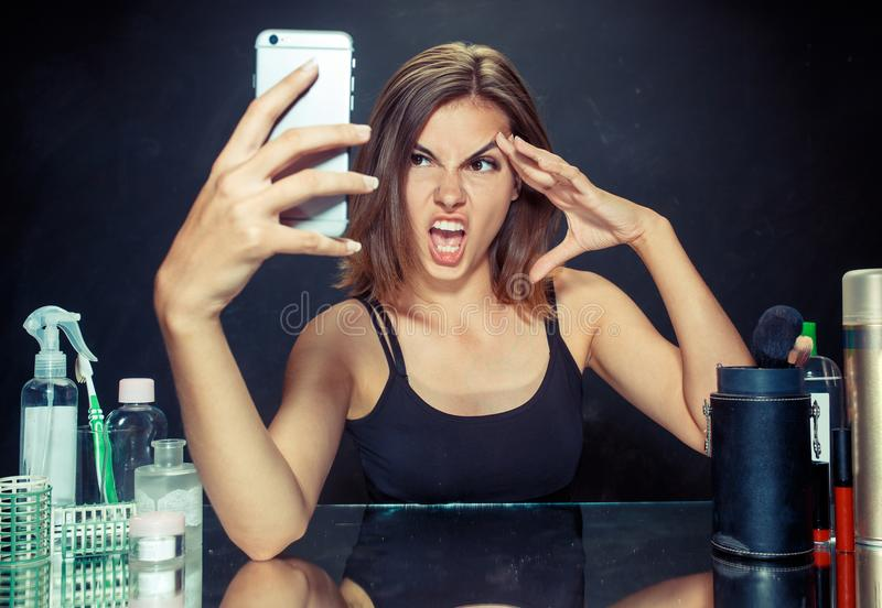 Beauty woman with makeup. Beautiful girl looking at the mobile phone and making selfie photo. Beauty woman after applying makeup.Beauty woman with makeup royalty free stock photography