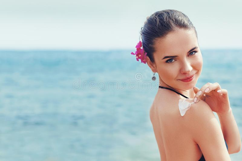 Beauty Woman applying sunscreen creme on  tanned  shoulder. Skin care. stock photography