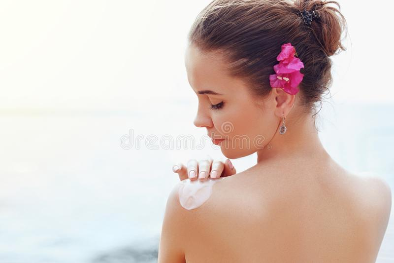 Beauty Woman applying sunscreen creme on  tanned  shoulder. Skincare. Body Sun protection sun cream. stock photo