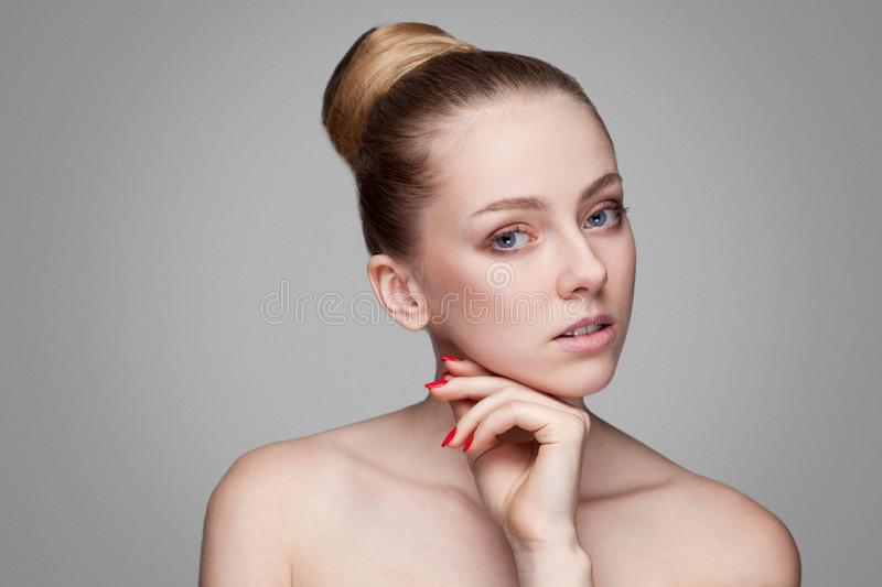 Beauty woman. Beautiful model girl with perfect fresh clean skin. Blonde brunette bun hair Youth and skin care concept. manicure stock photography