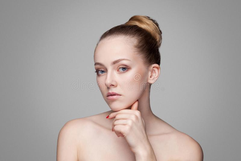 Beauty woman. Beautiful model with perfect fresh clean skin touch chin. Blonde brunette bun hair Youth and skin care concept. stock photos