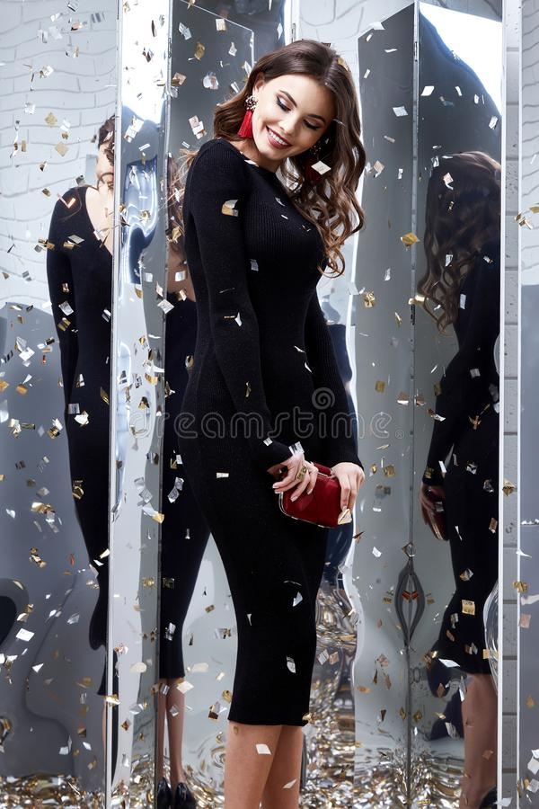 Beauty woman brunette curly hair makeup cosmetic face wear black. Skinny dress elegant style for celebrate party holiday Christmas New Year Valentine`s Day stock image