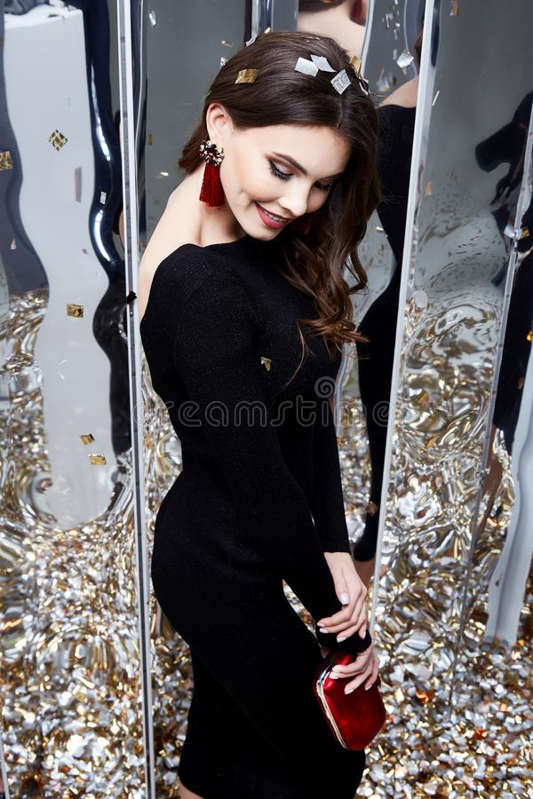 Beauty woman brunette curly hair makeup cosmetic face wear black. Skinny dress elegant style for celebrate party holiday Christmas New Year Valentine`s Day stock photo