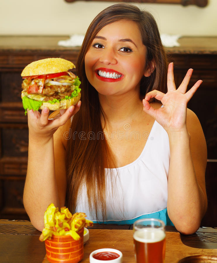 Beauty woman in cafe approving a delicious hamburger.  stock photo