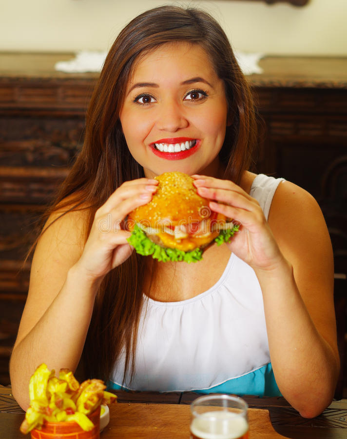 Beauty woman in cafe eating a delicious hamburger.  stock image