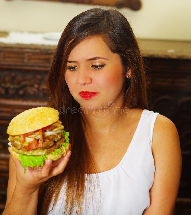 Beauty woman in cafe watching a delicious hamburger.  royalty free stock images