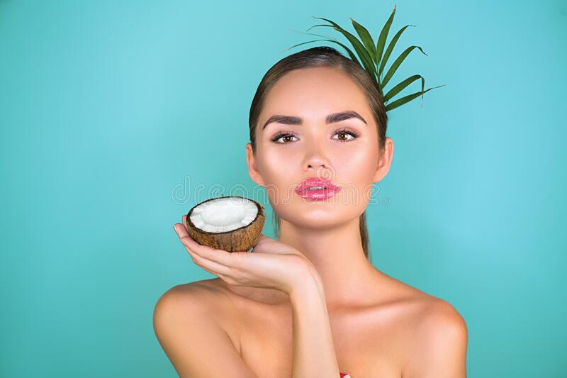 Beauty Woman with coconut Portrait. Spa model girl holding coco nut. Pretty young brunette woman face. Skin care stock images