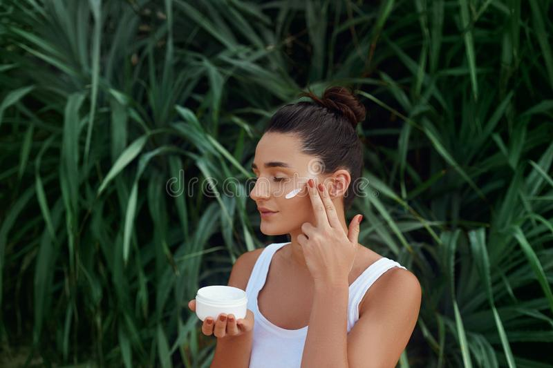 Beauty Woman Concept. Skin care.  Portrait of female model  holding and applying cosmetic moisturizing cream royalty free stock photo
