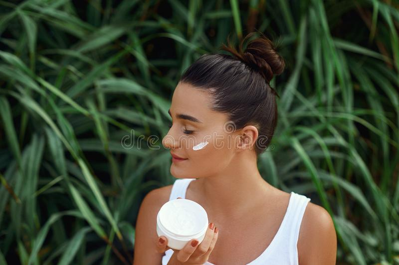 Beauty Woman Concept. Skin care.  Portrait of female model  holding and applying cosmetic moisturizing cream and touch own face. N royalty free stock photos