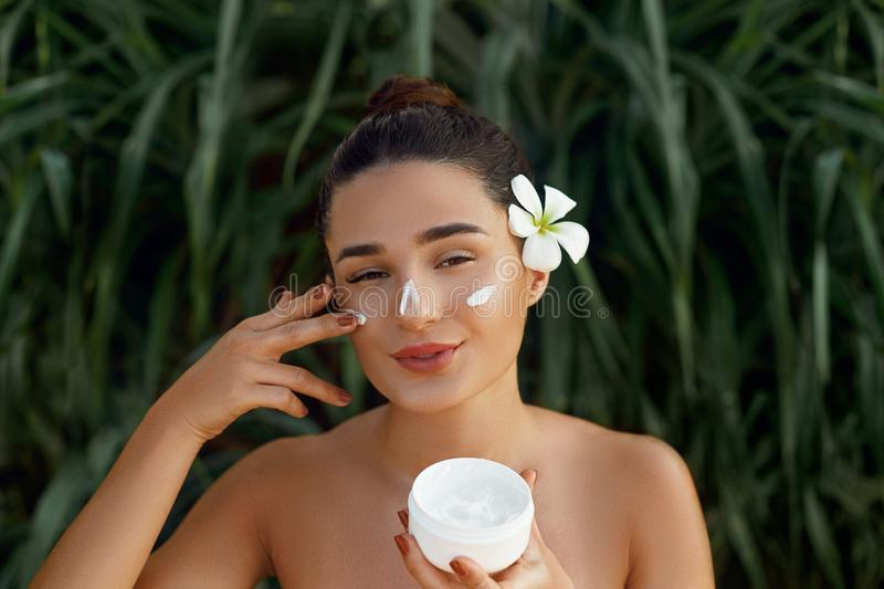 Beauty Woman Concept. Skin care. Young model with Soft skin holding cosmetic cream. Portrait of female applying moisturizing cream stock photo