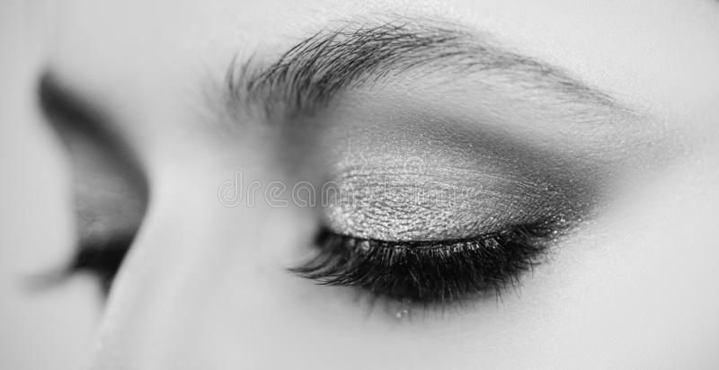 Beauty woman eyes. Makeup Model. Beautiful young girl in studio on gray background. Black and white. stock photography