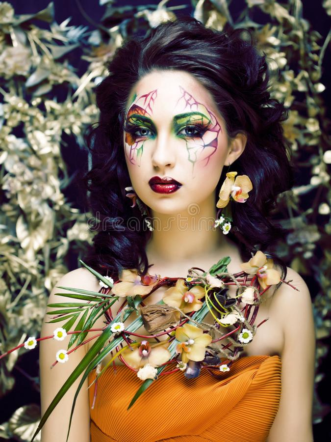Beauty woman with face art and jewelry from flowers orchids close up, creative makeup floral pattern background stock images