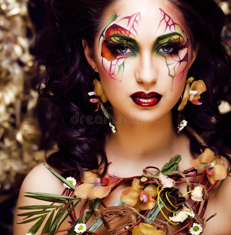 Beauty woman with face art and jewelry from flowers orchids close up, creative makeup floral pattern background stock photos
