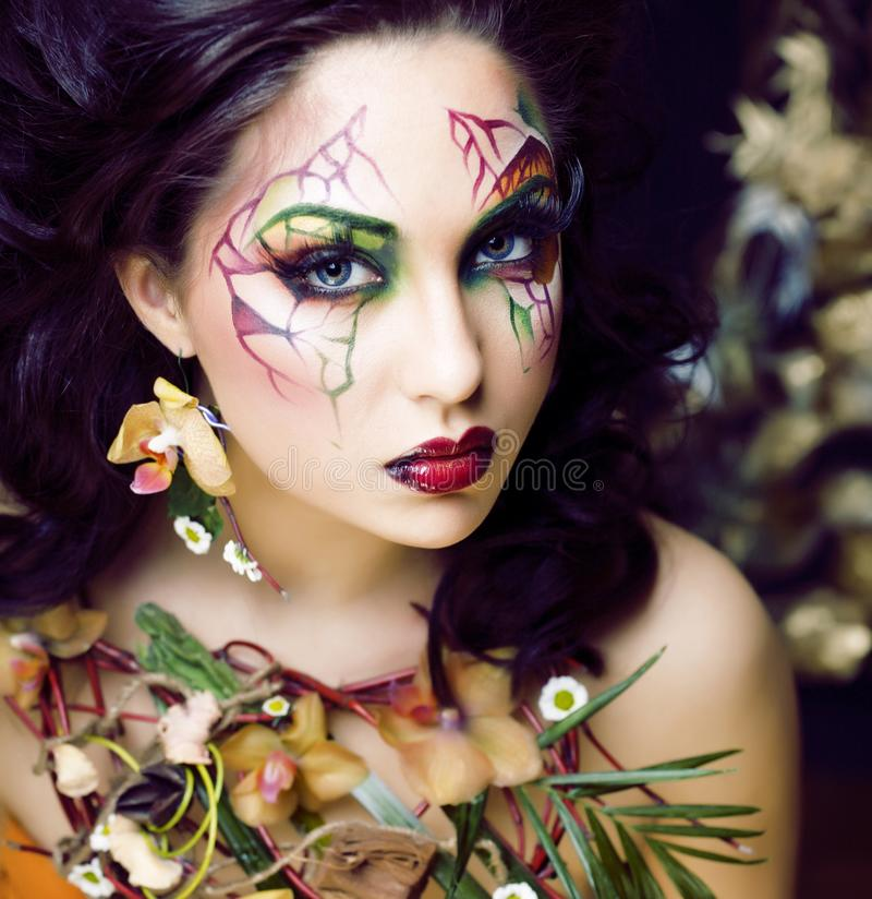 Beauty woman with face art and jewelry from flowers orchids close up, creative pattern makeup floral pattern background stock photos