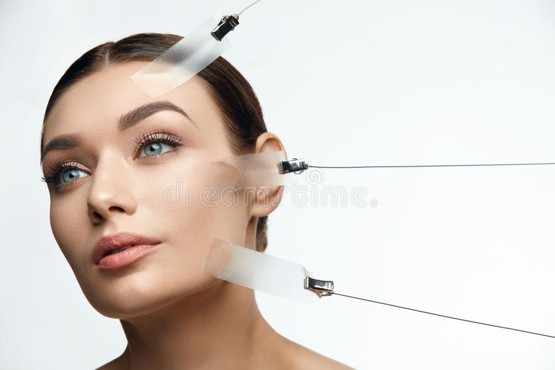 Beauty Woman Face During Face Skin Lift Treatment. On White Background. High Resolution stock images