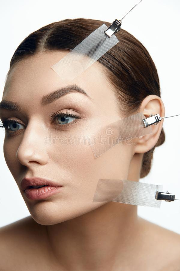 Beauty Woman Face During Face Skin Lift Treatment. On White Background. High Resolution royalty free stock photo