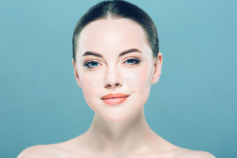 Beauty Woman face Portrait. Beautiful Spa model Girl with Perfect Fresh Clean Skin. Blue background. stock photos