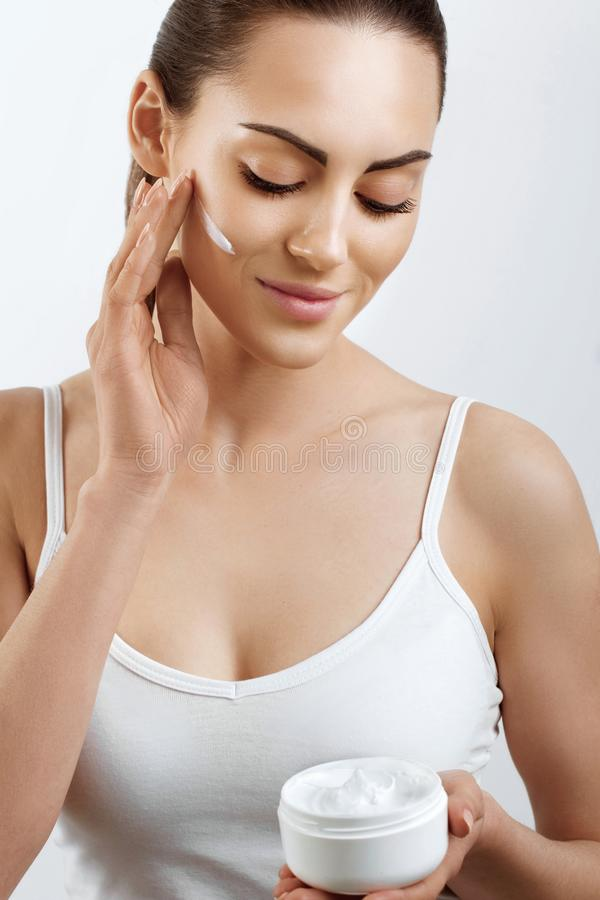 Beauty Woman Face Skin Care. Woman Face Skin Care. Portrait Of Attractive Young Female Applying Cream And Holding Bottle. Closeup Of Smiling Girl With Natural stock image