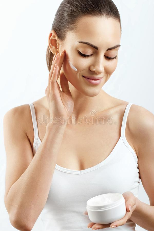 Beauty Woman Face Skin Care. Woman Face Skin Care. Portrait Of Attractive Young Female Applying Cream And Holding Bottle. Closeup Of Smiling Girl With Natural royalty free stock images