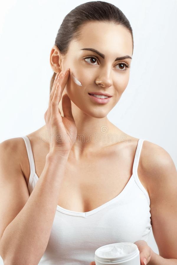 Beauty Woman Face Skin Care.  Woman Face Skin Care. Portrait Of Attractive Young Female Applying Cream  And Holding Bottle. stock photos