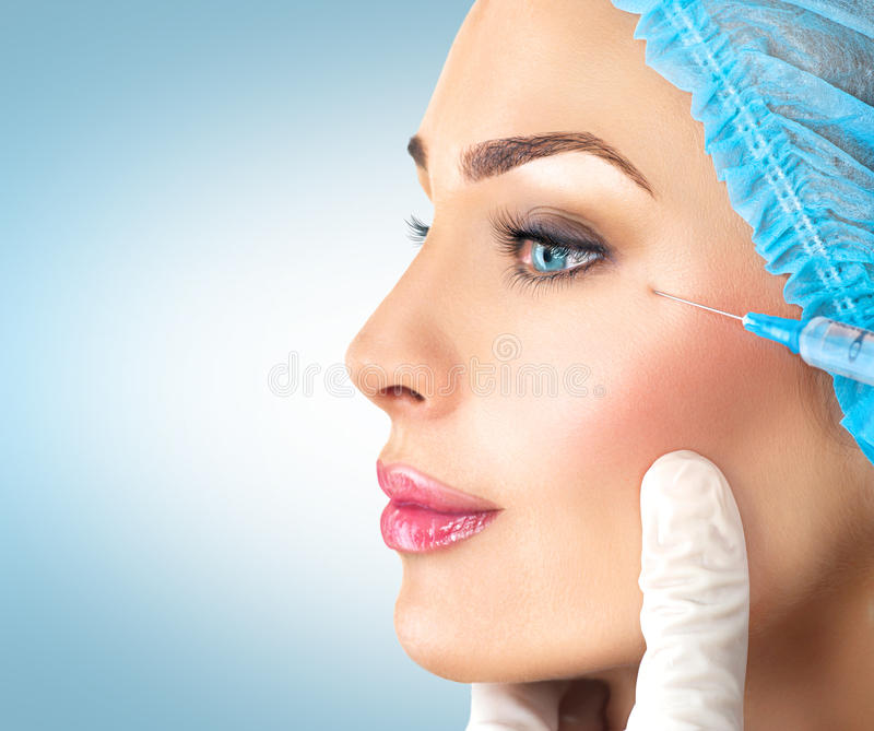 Beauty woman gets facial injections. Cosmetology stock image