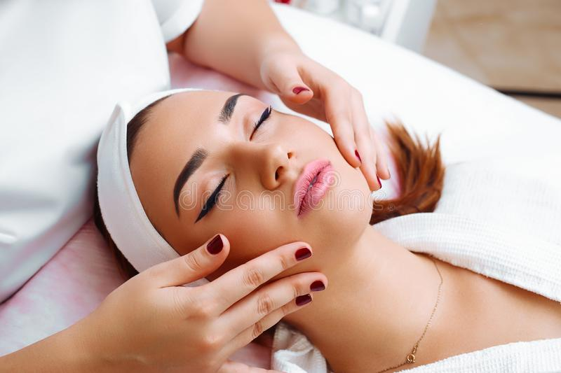 Cosmetic massage, facial treatment. Beauty woman having cosmetic massage, facial treatment, close up royalty free stock photo