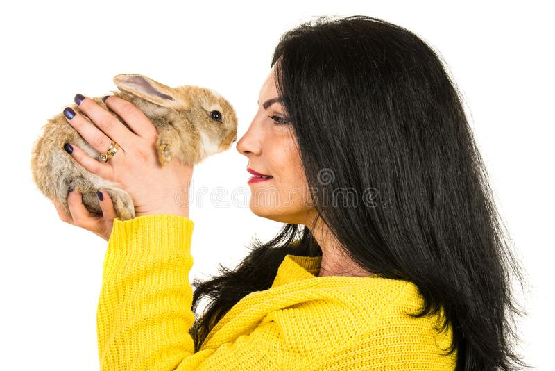 Beauty woman holding baby rabbit. Profile of woman holding and caring baby rabbit isolated on white background stock images