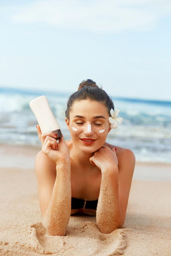 Beauty Woman holding bottles of sunscreen in her hands. Girl applying sun cream on face. Skin care. Sun protection . stock image