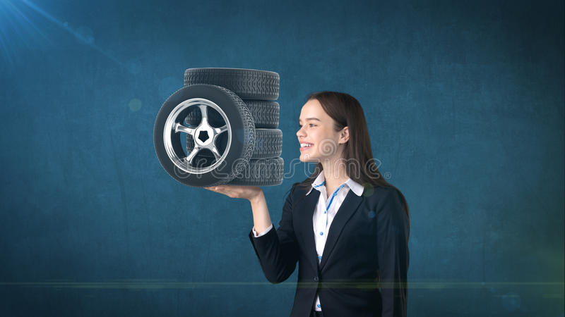Beauty woman holding car tires on the open hand palm, over isolated studio background. Business and auto concept. stock photos