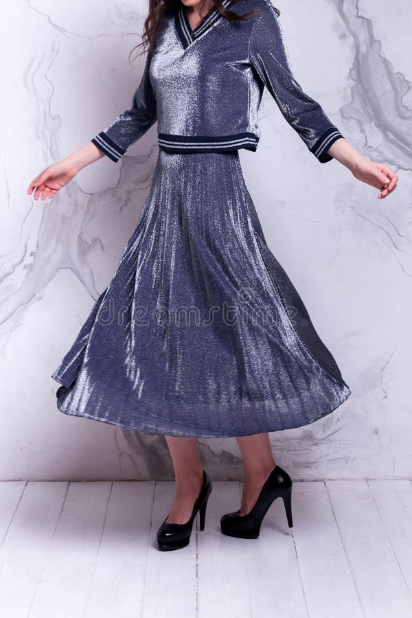New Year`s fashion trends. Beauty woman with long beautiful hair in a long silver shiny dress with high heels showing off her dress on studio background.Happy stock photos