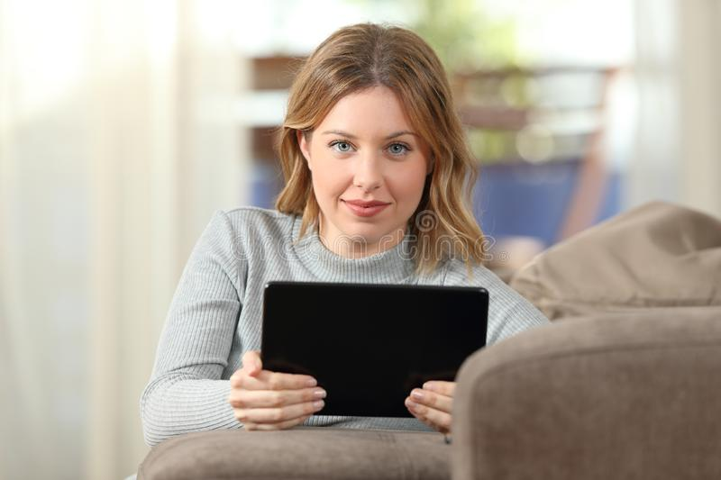 Beauty woman looking at camera holding tablet at home stock images