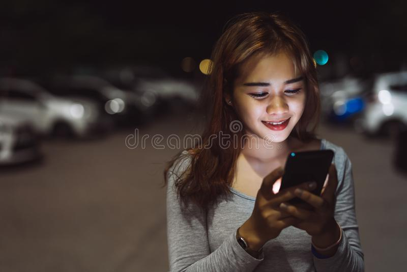 Beauty woman looking smartphone mobile phone at night on street stock photos