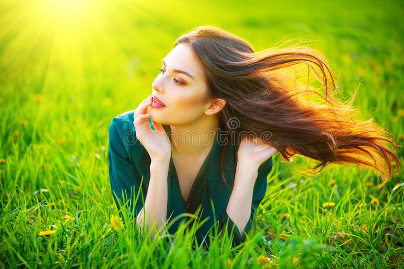 Beauty woman lying on the field enjoying nature. Beautiful brunette girl with healthy long flying hair. Summer green grass stock image