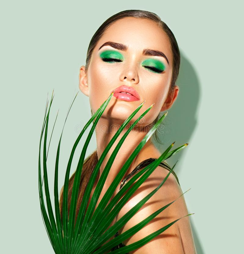 Beauty woman with natural green palm leaf. Portrait of model girl with perfect makeup, green eyeshadows royalty free stock images