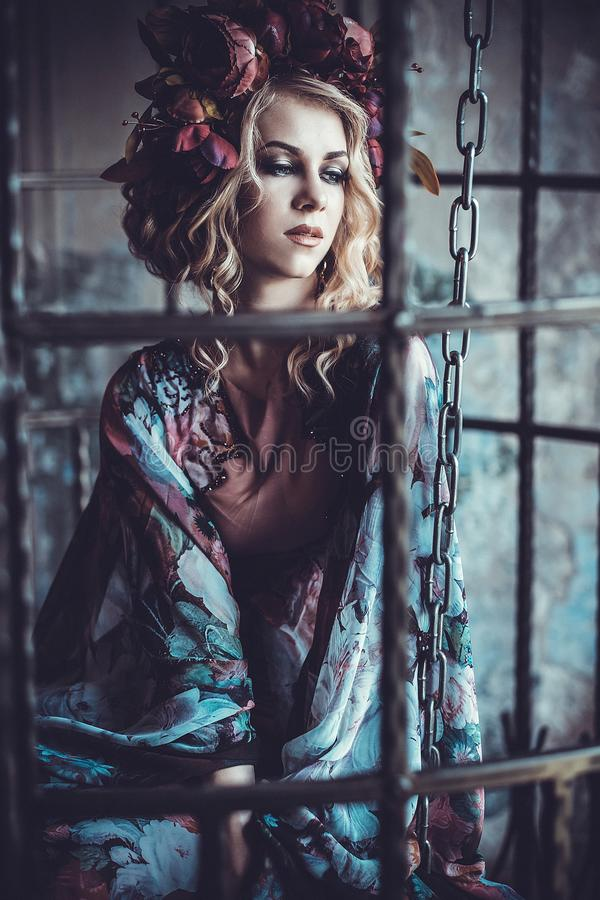 Beauty woman in the palace. Luxurious fashion stylish girl in cage. Flower dress and a wreath of flowers. Beauty woman in the palace. Luxurious fashion stylish stock images