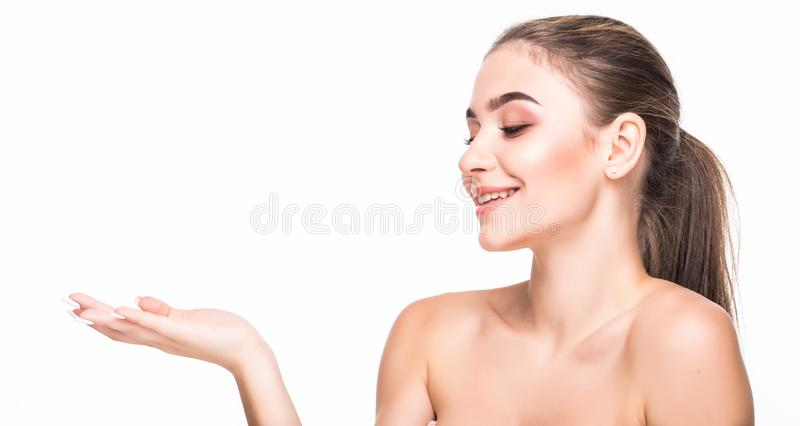 Beauty woman with perfect face skin. Portrait beautiful brunette spa girl showing empty copy space on the open hand palm for text. Beauty Spa Woman with perfect royalty free stock photos