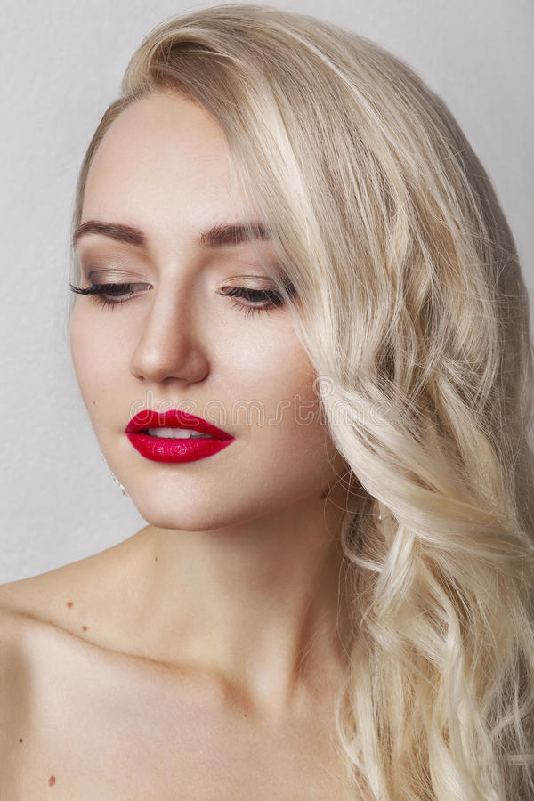 Beauty Woman with Perfect Makeup. Beautiful Professional Holiday Make-up. Red Lips and Nails. Beauty Girl`s Face isolated on Black stock image