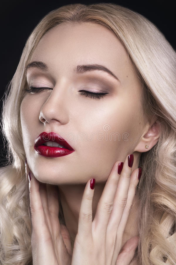 Beauty Woman with Perfect Makeup. Beautiful Professional Holiday Make-up. Red Lips and Nails. Beauty Girl`s Face isolated on Black. Background. Glamorous Woman royalty free stock images
