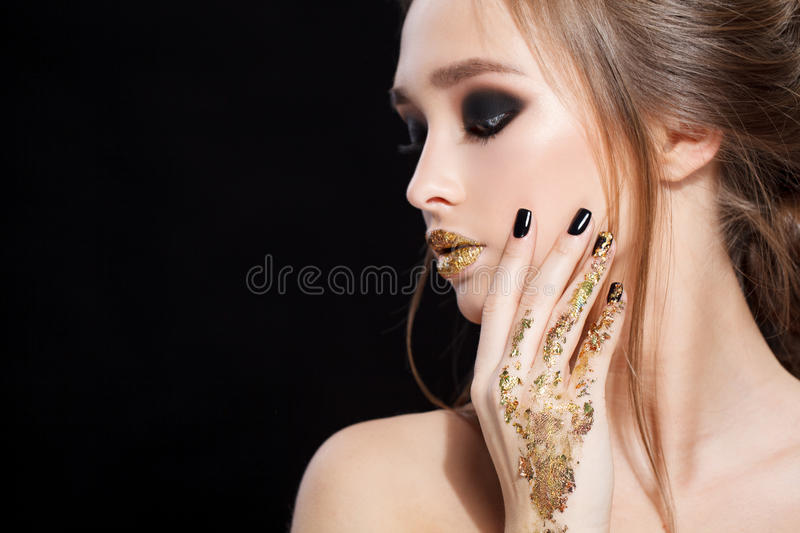 Beauty Woman Portrait. Professional Makeup and Manicure with gold foil glitter, smokey eyes. Black colors. Copy-space royalty free stock photography