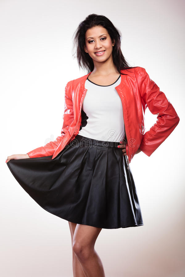 Beauty woman in red jacket. Fashion and style. Beauty gorgeous young mixed race woman wearing stylish red jacket coat and black leather skirt. Fashionable girl stock image