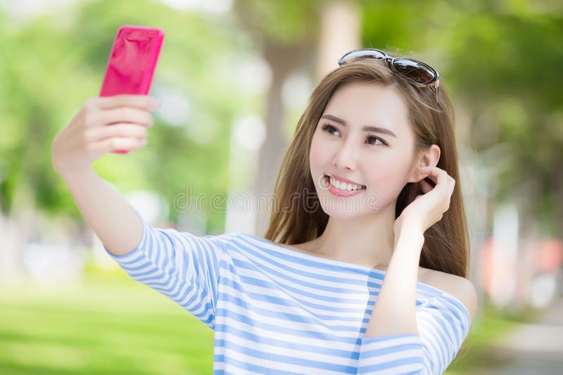 Woman selfie happily. Beauty woman selfie happily in the park stock photography
