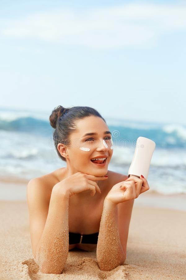 Beauty Woman Skin care sunscreen  holding bottles in her hands. Suntan Girl applying sun cream on face. stock photo
